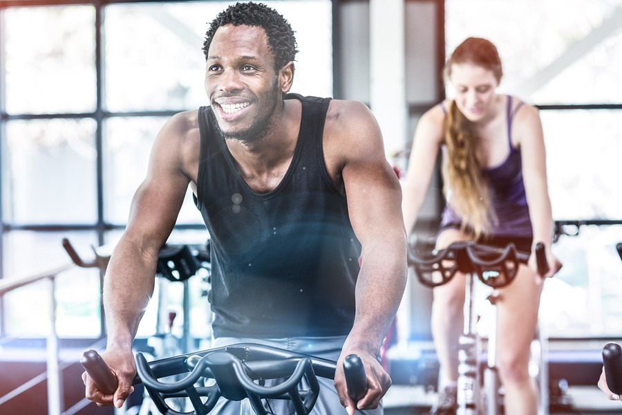 Fit man working out at spinning class in gym