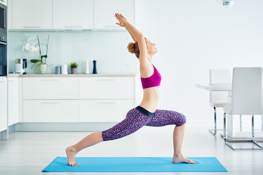 Portrait of fit red haired woman doing yoga exercises at home on floor: stretching muscles standing